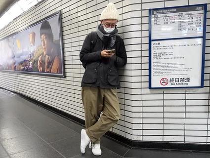 Man reading on his smart phone, Shinjuku Railway Station, Tokyo, Japan.