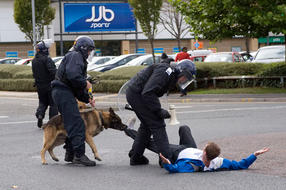 An EDL protester that was rampaging through Bradford is lying in the street as he gets bitten by a police dog as a further officer is shouting at him.