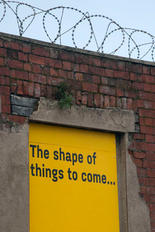 The shape of things to come... street art on a former entrance of a derelict barbed wired building, Sheffield.