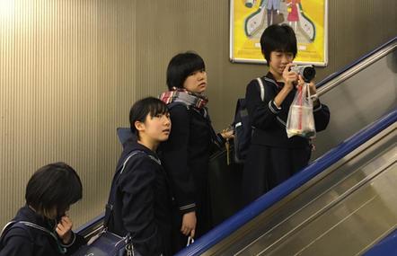 School children taking photos whilst traveling on an escalator, Tokyo Railway Station.