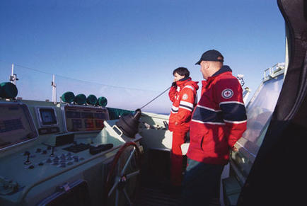 Coxswain Guido Förster and Olaf Wittorff steering from the upper deck, Lübeck Bay, Germany.