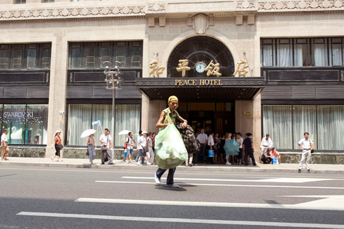 A homeless man walking past the expensive Peace Hotel, Shanghai.