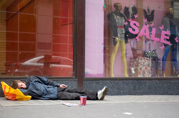 A homeless man sleeping whilst begging in central London.