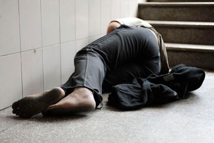 A homeless man sleeping rough at Shanghai Train Station, Shanghai, China.
