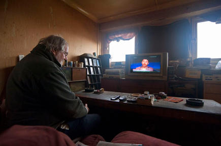 Jacobs, effected by the Bedroom Tax, watching news on the increased usage of food banks on TV in his council flat in Highgate, Birmingham.