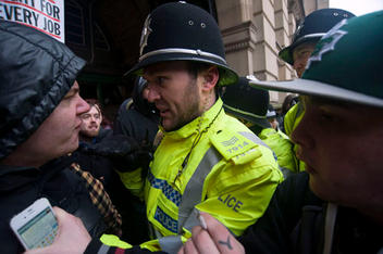 Police confront protesters who blockade the entrances to the Birmingham Council House to prevent councillors to enter for their budget meeting as the Labour run council plans to vote for £102m cuts.