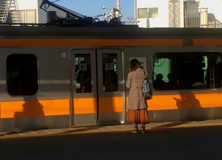 Woman waiting for train, Keio-Inokashira Line, Tokyo, Japan.