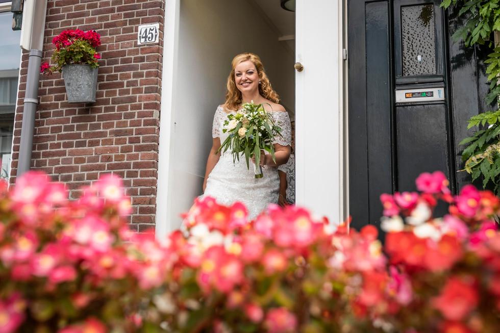Bruidsfoto van Elise die het huis verlaat