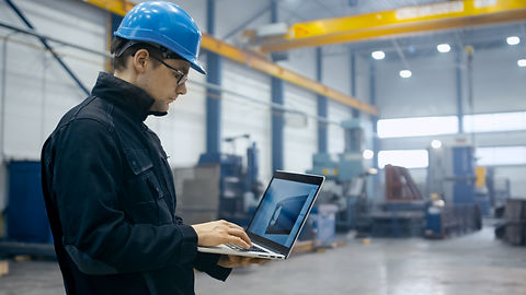 Factory worker in a hard hat is using a laptop computer with an engineering software.jpg