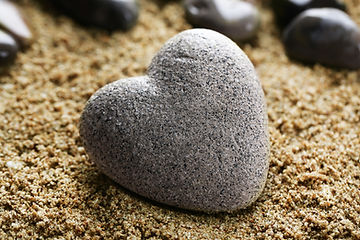 Grey stone in shape of heart, on sand background.jpg