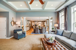 stone fireplace, custom curtains, swivel chairs, coffered ceiling, sofa with chaise, leather cocktai