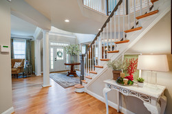 Formal foyer, grand entry, waterfall staircase, floral arrangement