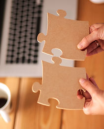 Business woman holding and pointing to a puzzle piece.jpg