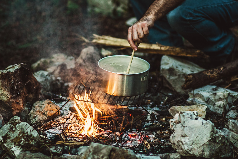Man with muddy arm stirring pot of hot water and vegetables over fire-pit campfire