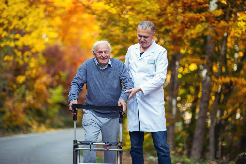 older man at long-term care facility walking with staff member