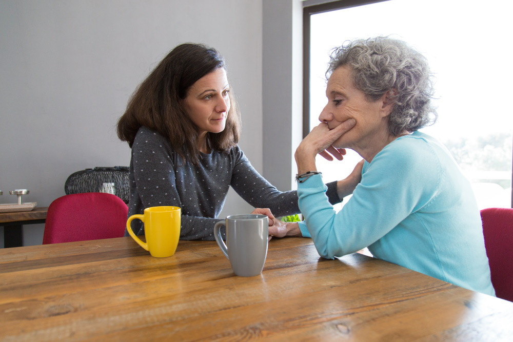 senior woman with anxiety sitting at a table with her daughter