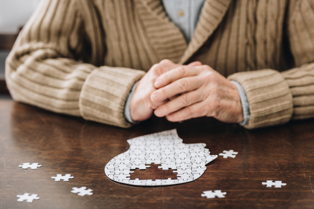A senior man with an incomplete puzzle representing dementia