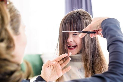 Laughing child having hair cut