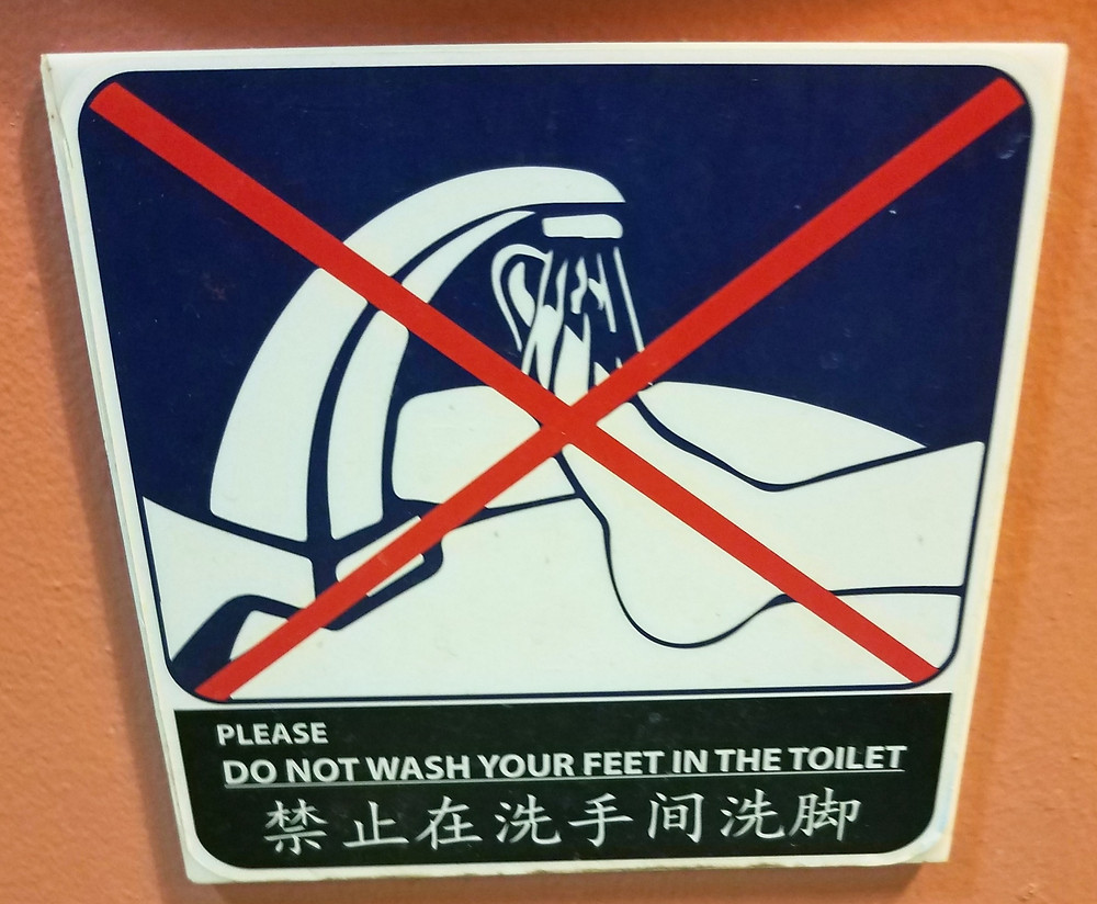 A sign telling people not to wash their feet in the sink or toilet
