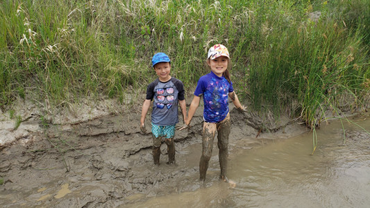Kids getting muddy by the river, camping at Dinosaur Provincial Park