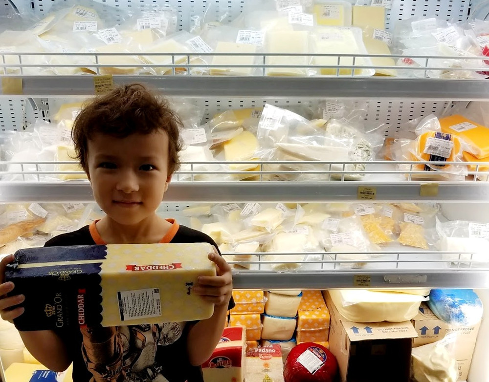 Boy holding giant cheese block