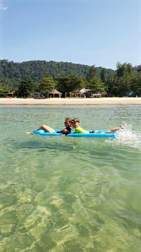 Kids swimming in the clear blue water on Koh Lanta