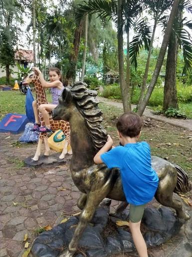 Kids having fun on the alphabet sculptures in Thara Park, Krabi, Thailand