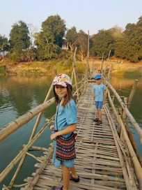 Kids walking over bamboo bridge