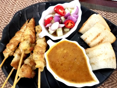 Chicken skewers in Chiang Mai, served with peanut sauce, bread and salad.