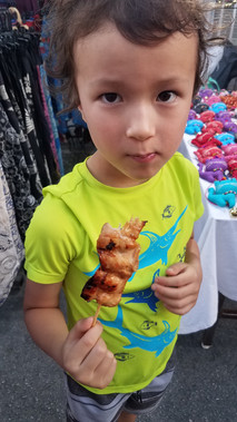 eating a chicken skewer at the night market in Thailand