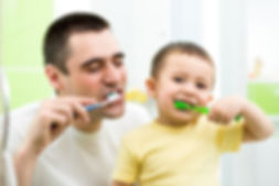 Family brushing teeth with dad and child