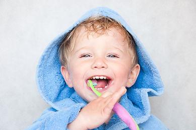 Happy child brushing teeth at dentist office