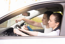 young-woman-driving-man-pointing-direction.jpg