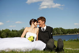 A bride and groom sat on grass near a lake with their heads touch in Cardiff, South Wales