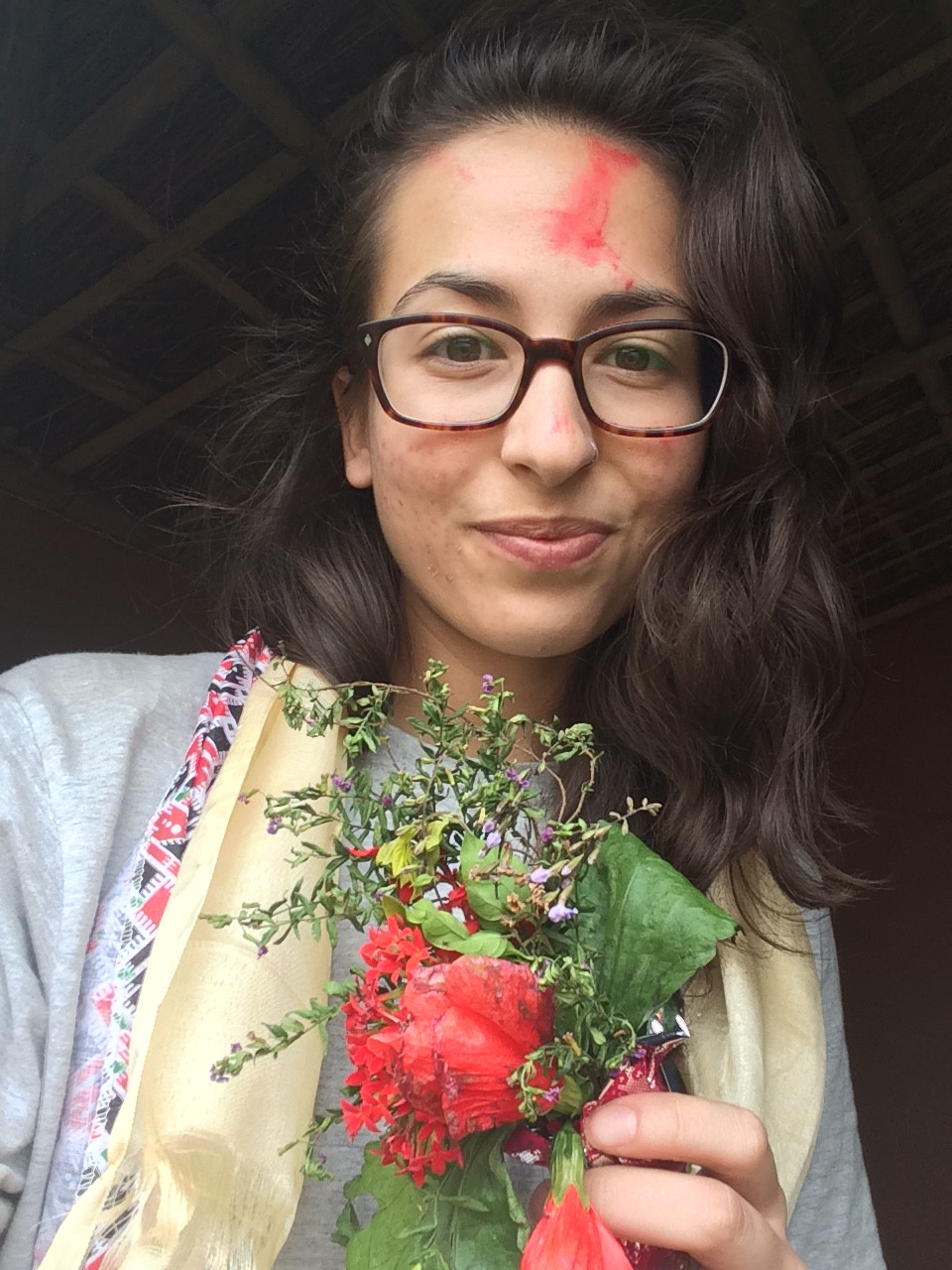 girl holding flowers with vermillion on face