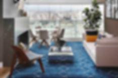 Sala com pé direito duplo, pendente floral, mosaico português, piso de madeira de demolição, tapete geométrico azul, mesa de centro espelhada, mesa de jantar redonda com cadeiras estofadas, lareira ecológica embutida, revestimento marmorizado preto, jardim vertical, vaso e quadros com tema de folhagem.