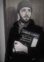Picture of young man with scarf, beard, and holding Great Lakes books