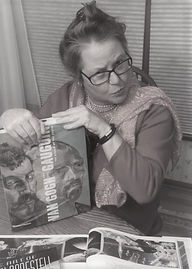 Picture of an older lady with glasses a scarf and art books