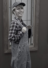 Picture of woman with overalls, plaid shirt and blonde hair