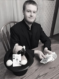 Picture of a young man with a black coat, mullet and cards