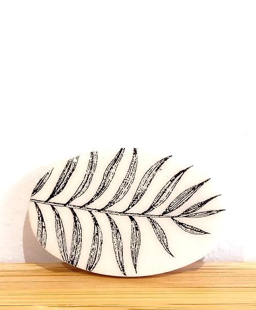 Broche en faïence ovale à motif fougère noire et écrue de la céramiste marseillaise Stéphanie Cahorel