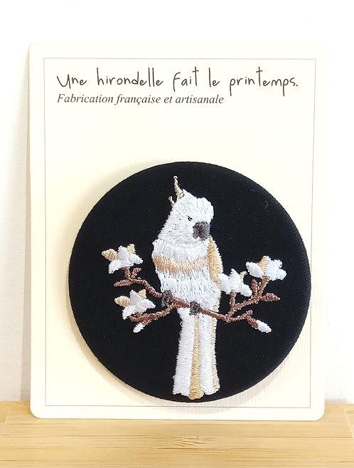 Badge brodé motif cacatoès blanc sur fond noir Une hirondelle fait le printemps