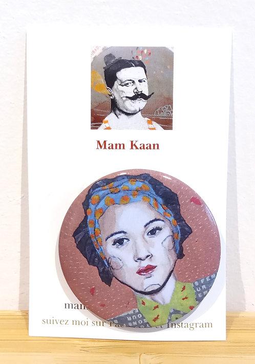 Badge 45mm représentant un portrait de femme avec un bandeau à pois orange dans les cheuveux tiré d'un tableau de Mam Kaan