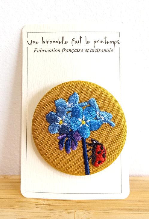 """Broche brodée pm motif coccinelle sur fleurs bleues """"Une Hirondelle Fait Le Printemps""""."""