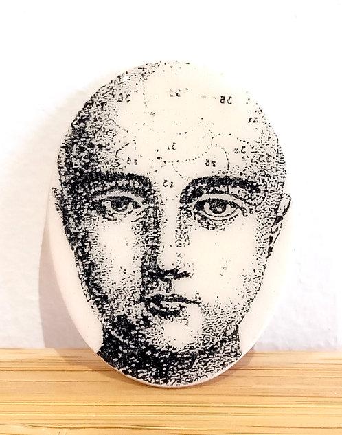 Broche en faïence ovale de la céramiste Stéphanie Cahorel représentant un visage tiré d'une planche d'anatomie noir sur écru.