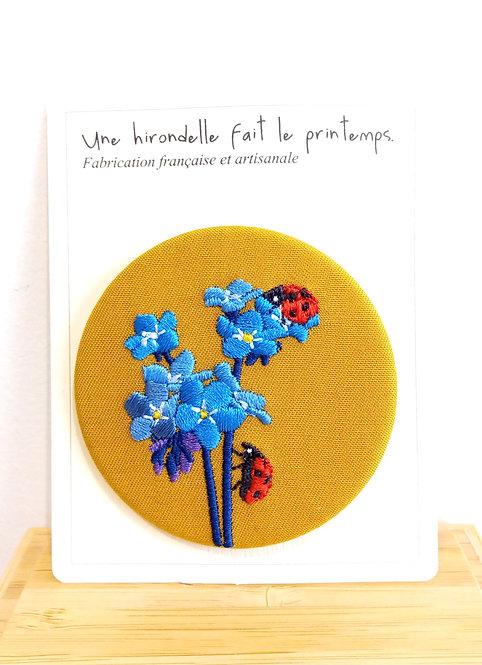 Broche brodée motif fleurs bleues et coccinelles sur fond ocre Une hirondelle fait le printemps