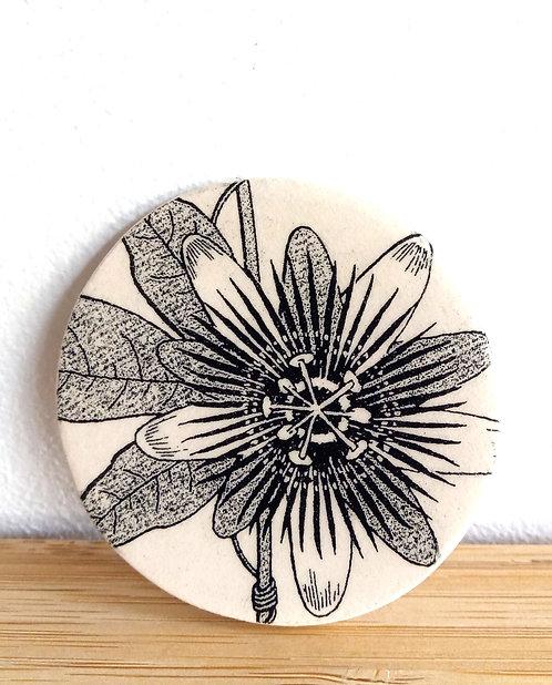 Broche ronde en faïence motif passiflore noir sur fond écru de Stéphanie Cahorel, artiste marseillaise