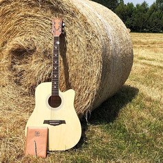 KJerrie's guitar and lyric book leaning against a hay bale