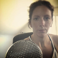 Kerrie in her home recording studio in front of a microphone