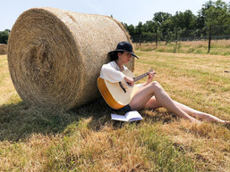 Kerrie Fuller writing and playing guitar, sitting in a field leaning against a haybale